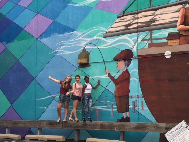 From Left to Right: Carrie, Jo and Alaysia in front of a mural in Fells Point